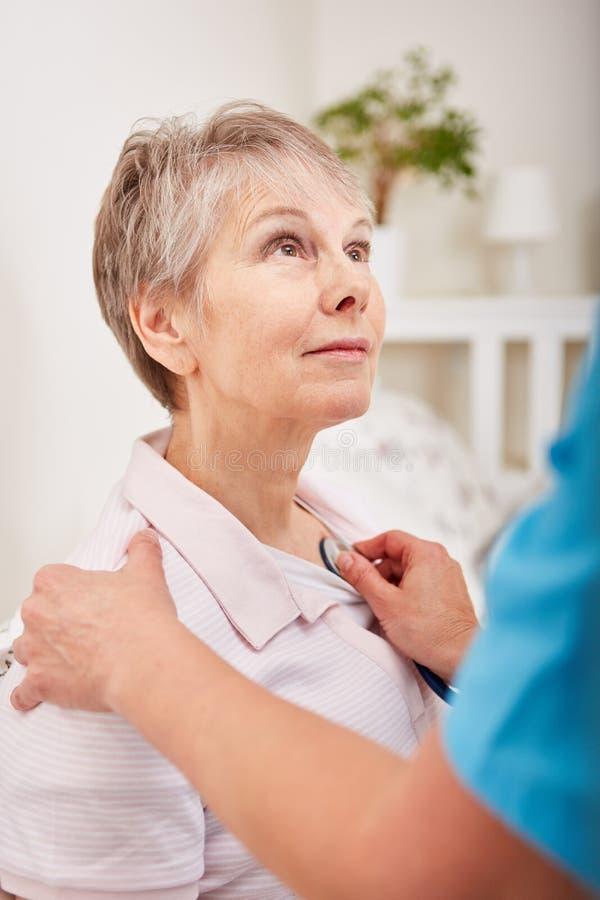 L'infermiere esamina la donna senior con demenza fotografia stock libera da diritti