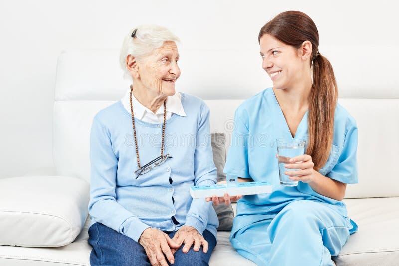 L'infermiere femminile dà a droga senior una droga fotografia stock