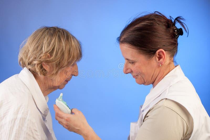 L'infermiere legge la temperatura della donna senior immagini stock libere da diritti