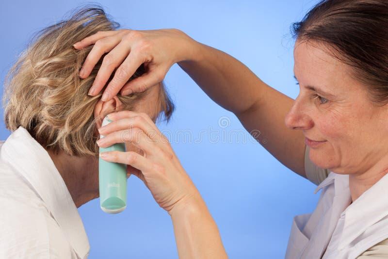 L'infermiere misura la temperatura alla donna senior immagini stock