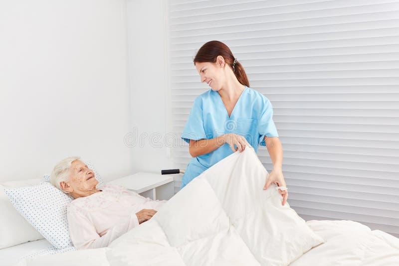 L'infermiere si occupa di un anziano malato immagini stock