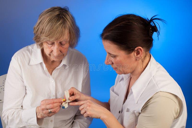 L'infermiere sta aiutando una donna anziana con il suo farmaco immagini stock libere da diritti