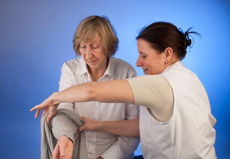 L'infermiere sta aiutando una donna anziana con vestirsi immagini stock
