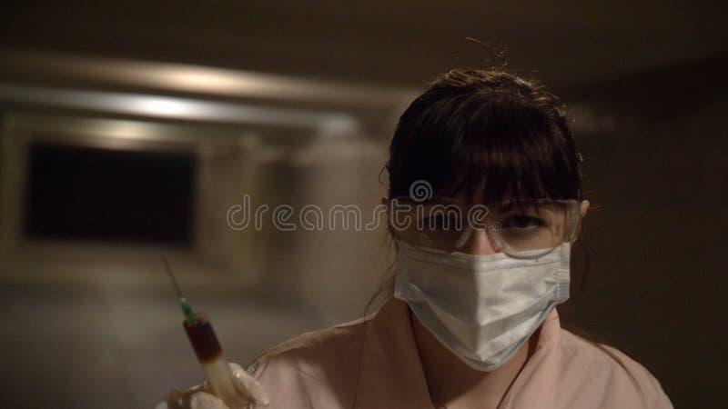 L'infermiere va fare un'iniezione esamina il timore di orrore della macchina fotografica di panico fotografia stock