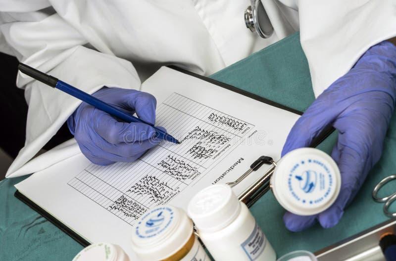 L'infirmière écrit la dose pour le patient dans un hôpital photo libre de droits