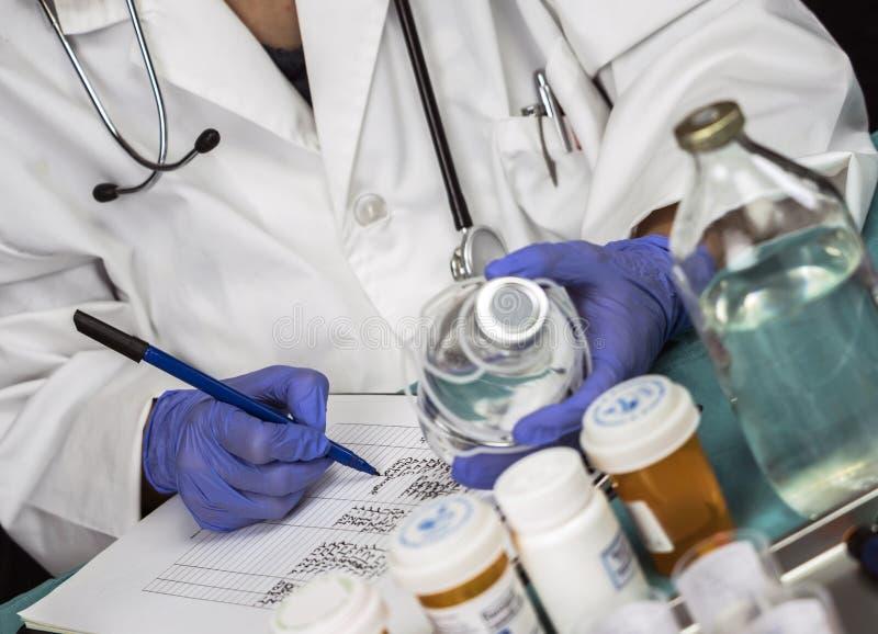 L'infirmière écrit la dose pour le patient dans un hôpital photos libres de droits