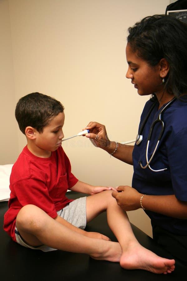 L'infirmière contrôle le jeune patient photographie stock libre de droits