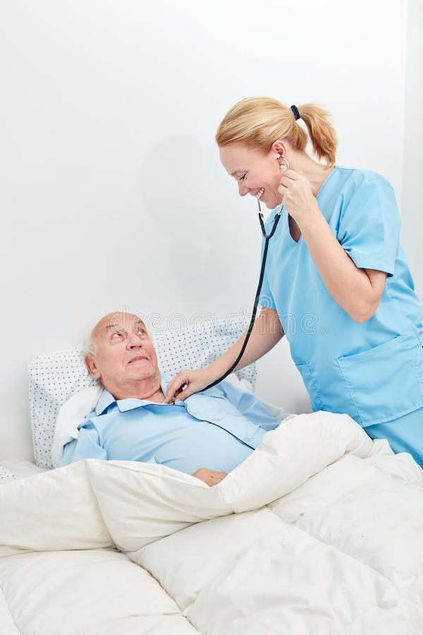 L'infirmière examine l'aîné malade photos libres de droits