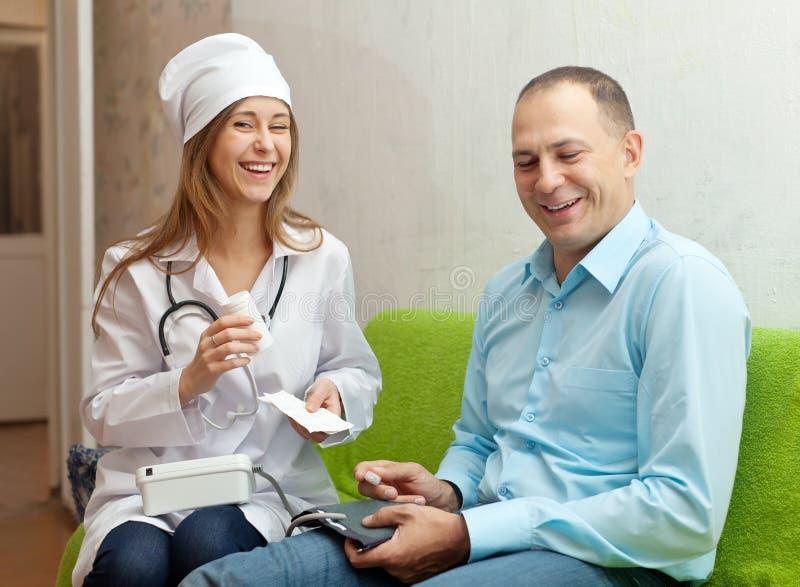 L'infirmière heureuse donne au patient le médicament photo stock