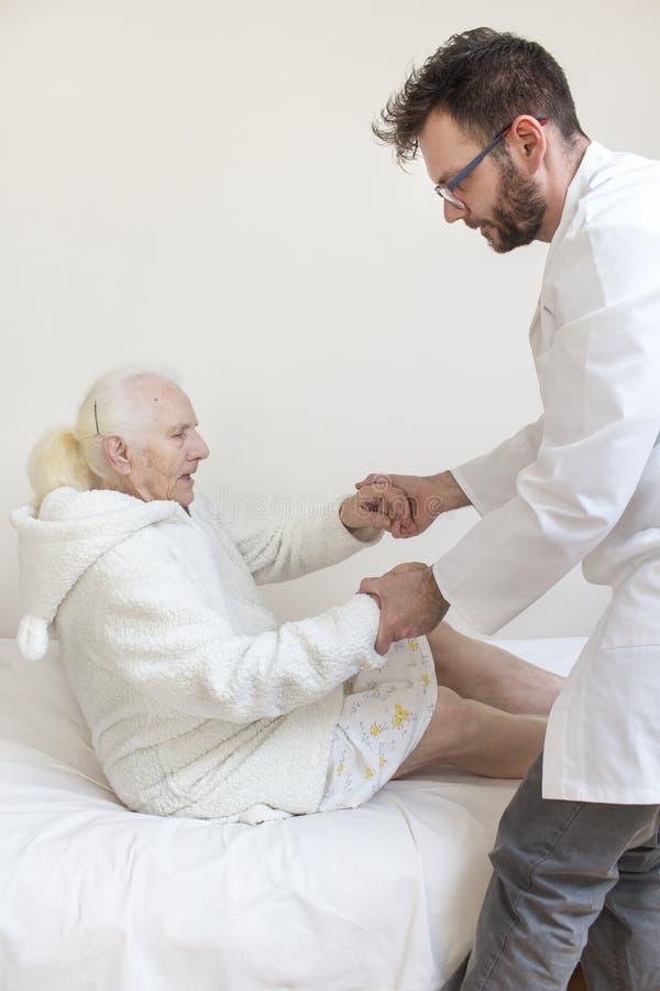 L'infirmière masculine aide à se lever du lit de dame âgée image libre de droits