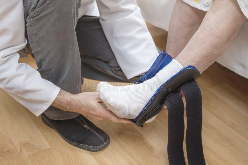 l'infirmière masculine assume un stabilisateur de cheville sur la jambe de dame âgée photo libre de droits