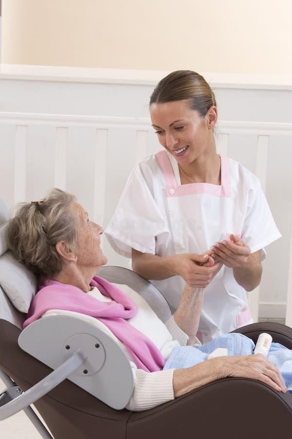 L'infirmière ou le travailleur social aide une femme agée avec des soins de la peau image libre de droits