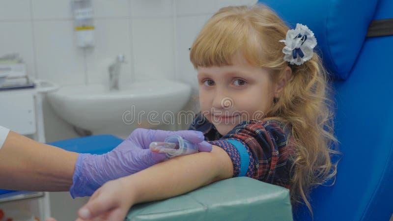L'infirmière prélève la prise de sang d'une veine dans le bras de la petite fille photo libre de droits