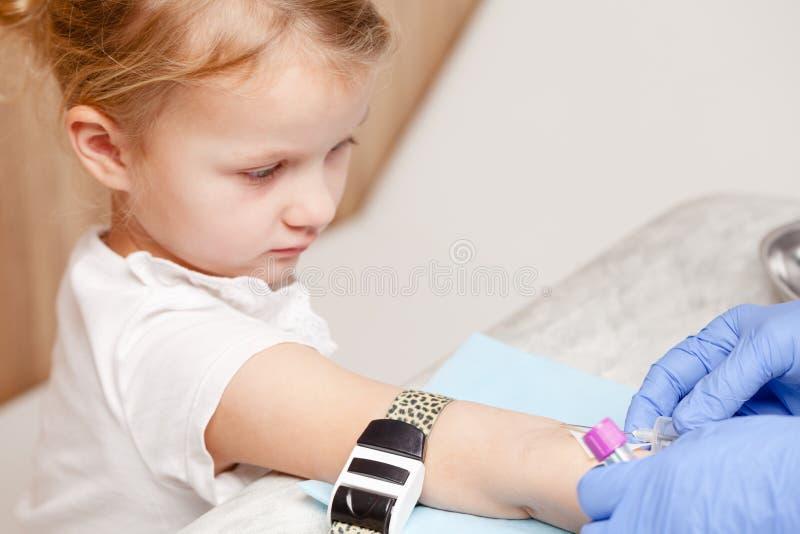 L'infirmière prélève une prise de sang de petites filles arment - le TSV pédiatrique photo stock