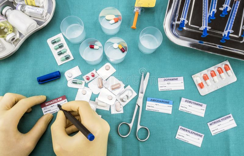 L'infirmière préparant le médicament d'hôpital, écrivent des données en difficulté aux labels médicaux de tâche photo stock