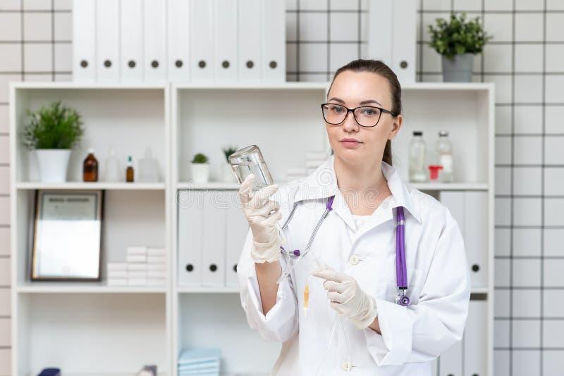 L'infirmière prépare un compte-gouttes avec une solution de médecine photographie stock