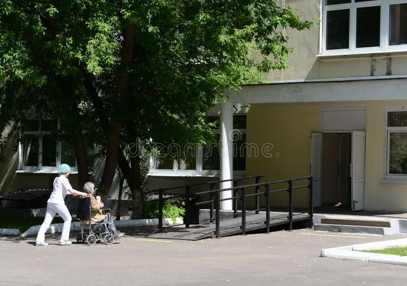 L'infirmière roule une femme agée dans un fauteuil roulant sur le territoire de l'hôpital des vétérans des guerres photographie stock