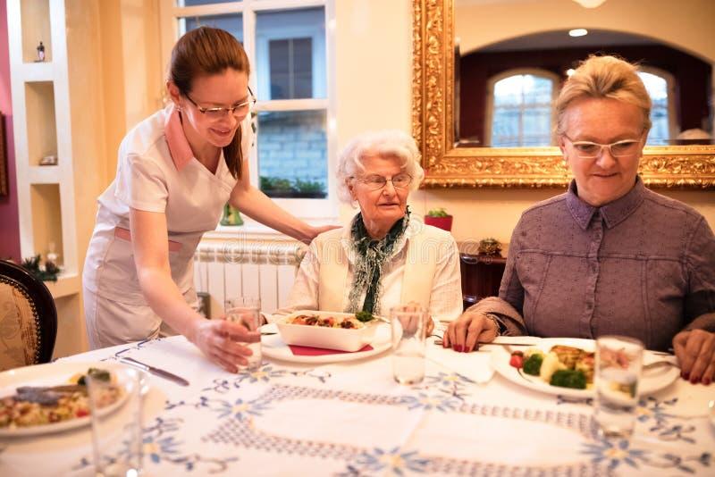 L'infirmière soigneuse met une table pour le dîner aux patients au hom de soins images stock