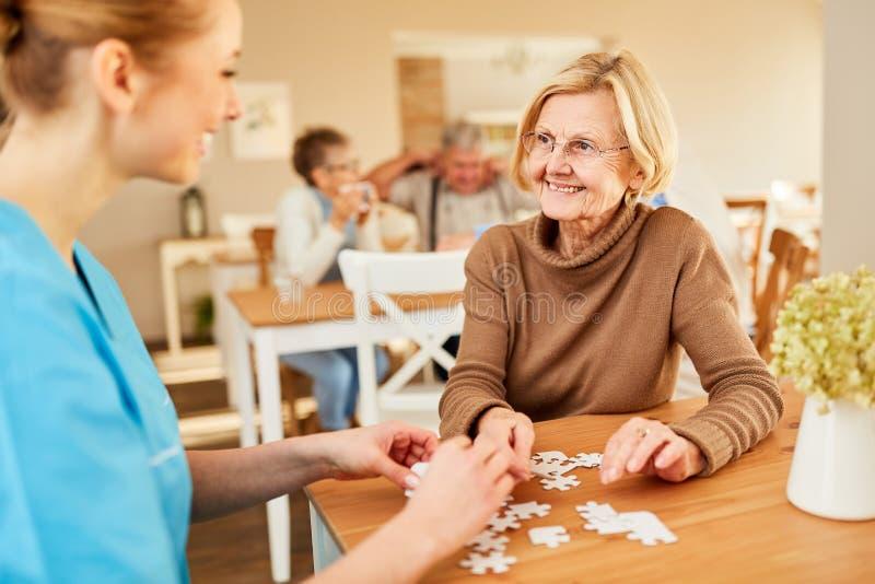 L'infirmière supérieure démente joue le puzzle images stock