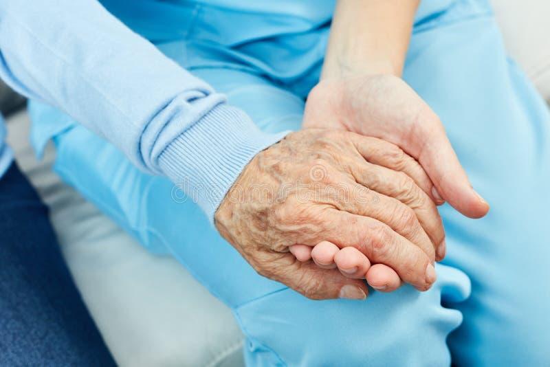 L'infirmière tient la main d'un vieillard photo stock