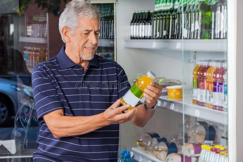L'information de lecture d'homme sur Juice Bottle image stock