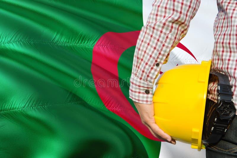 L'ingénieur algérien tient le casque de sécurité jaune avec onduler le fond de drapeau de l'Algérie Concept de construction et de image libre de droits