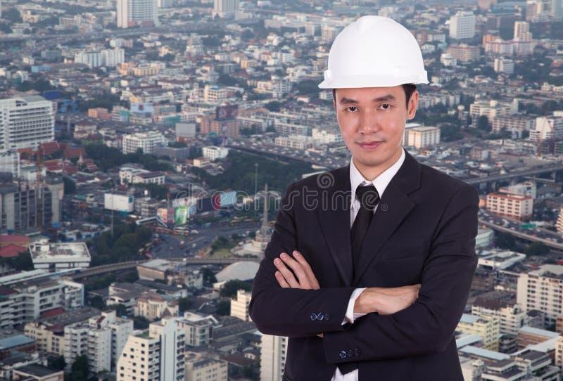 L'ingénieur dans le casque avec des bras a croisé, fond de ville photo libre de droits