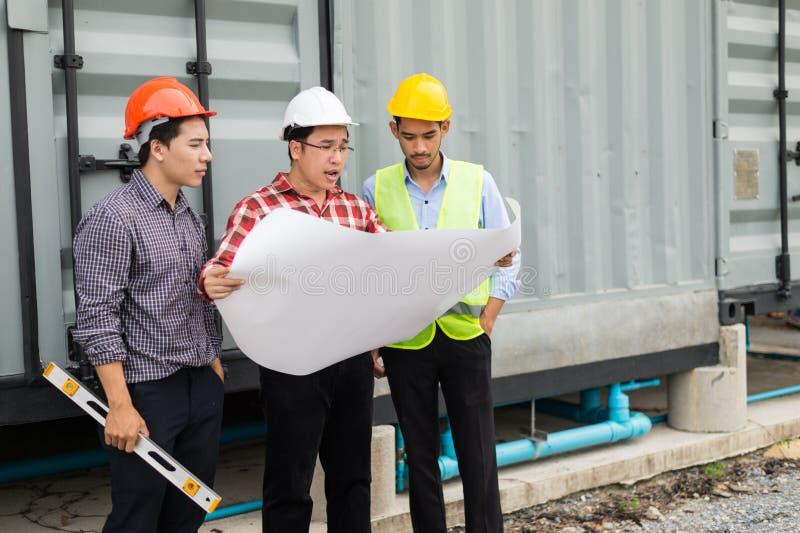 L'ingénieur et la construction team le casque de sécurité et le modèle de port en main ils travaillent à vérifier le progrès de l photographie stock libre de droits