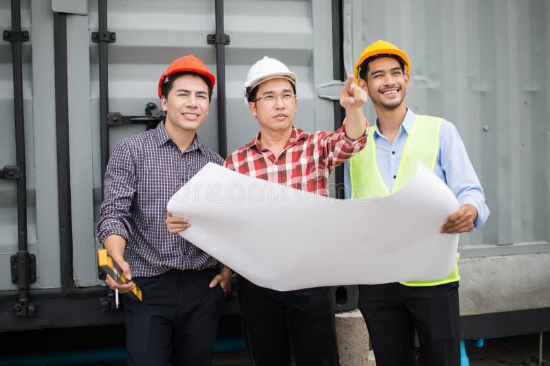 L'ingénieur et la construction team le casque de sécurité et le modèle de port en main ils vérifient le progrès du chantier de co photo libre de droits
