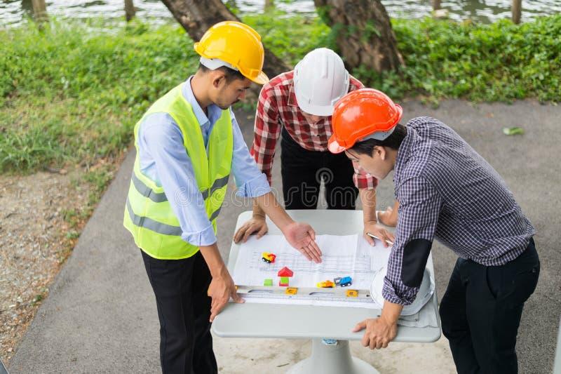L'ingénieur et la construction team le casque de sécurité et le modèle de port de regard sur la table image stock