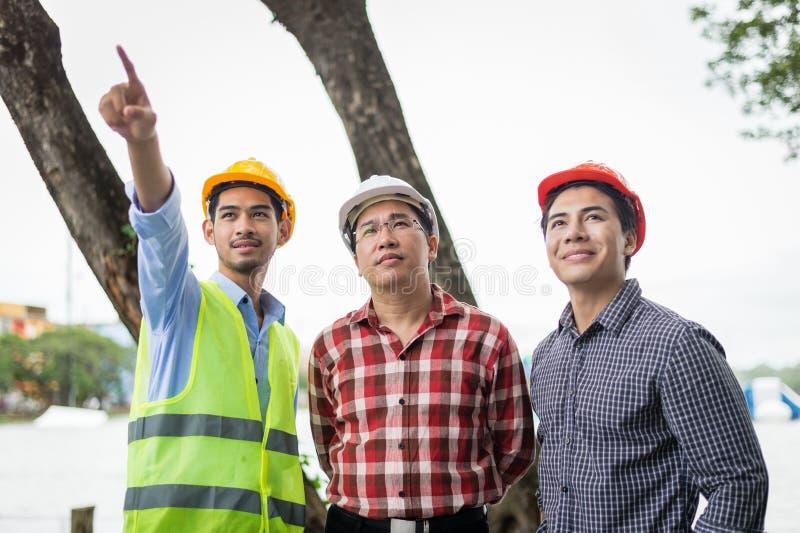 L'ingénieur et la construction team le casque de sécurité de port et le travail au chantier de construction image libre de droits