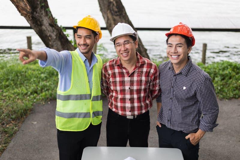 L'ingénieur et la construction team le casque de sécurité de port et le travail au chantier de construction ils sourient après co photos stock