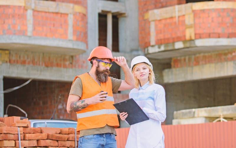 L'ingénieur et le constructeur de femme communiquent au chantier de construction Discuter le plan Concept de communication d'équi images libres de droits