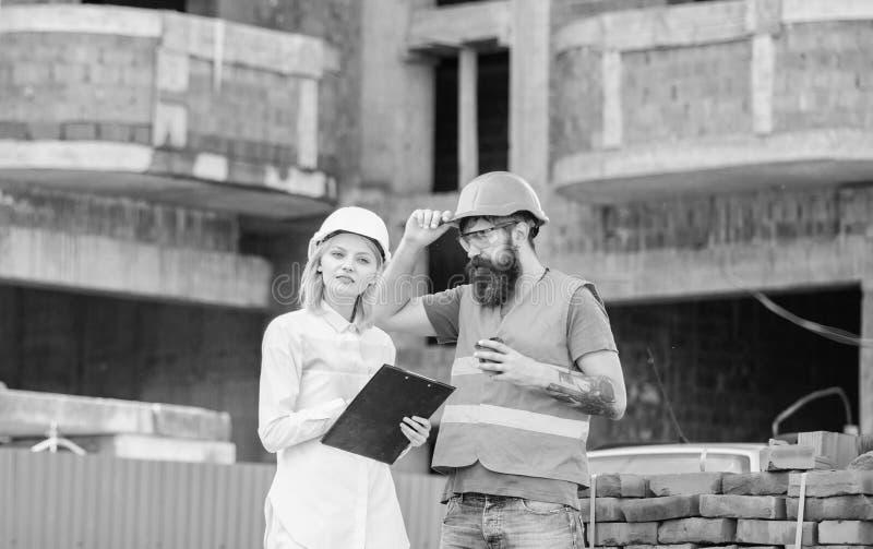 L'ingénieur et le constructeur de femme communiquent au chantier de construction Discuter le plan Concept de communication d'équi image stock