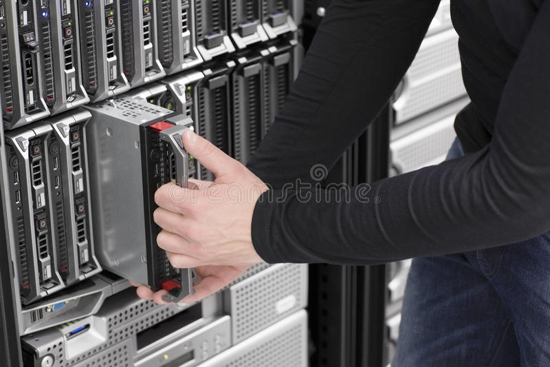 L'ingénieur informatique maintiennent le serveur de lame au centre de traitement des données image libre de droits