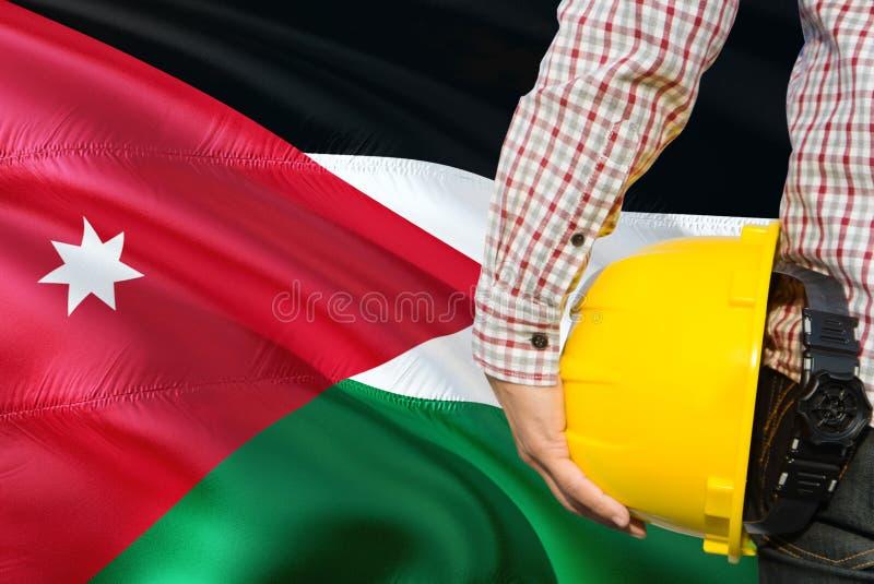 L'ingénieur jordanien tient le casque de sécurité jaune avec onduler le fond de drapeau de la Jordanie Concept de construction et photographie stock libre de droits