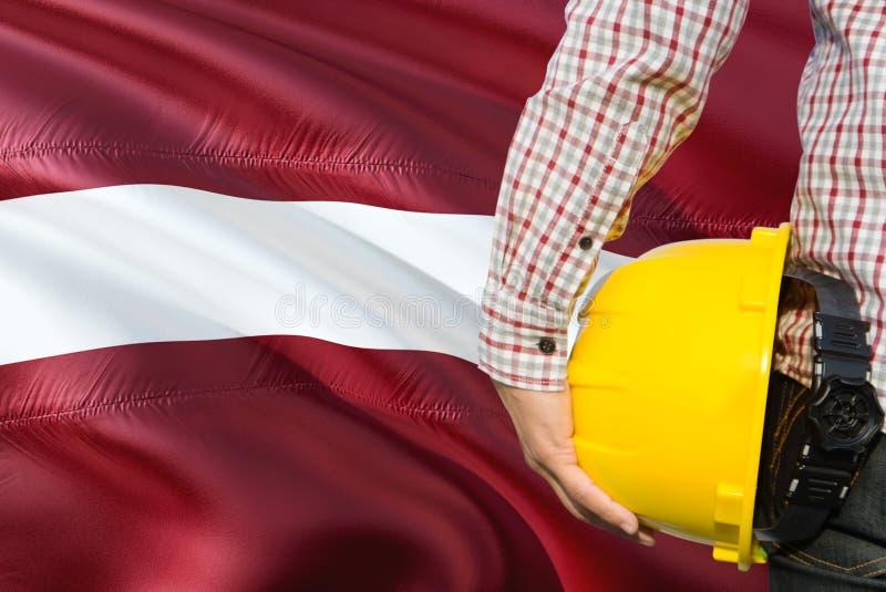 L'ingénieur letton tient le casque de sécurité jaune avec onduler le fond de drapeau de la Lettonie Concept de construction et de images libres de droits
