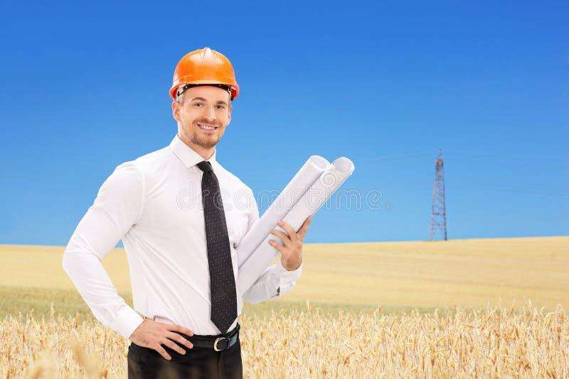 L'ingénieur masculin tenant la construction prévoit dans un domaine photographie stock libre de droits