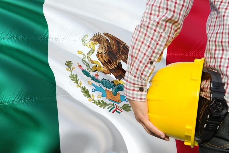 L'ingénieur mexicain tient le casque de sécurité jaune avec onduler le fond de drapeau du Mexique Concept de construction et de b image libre de droits