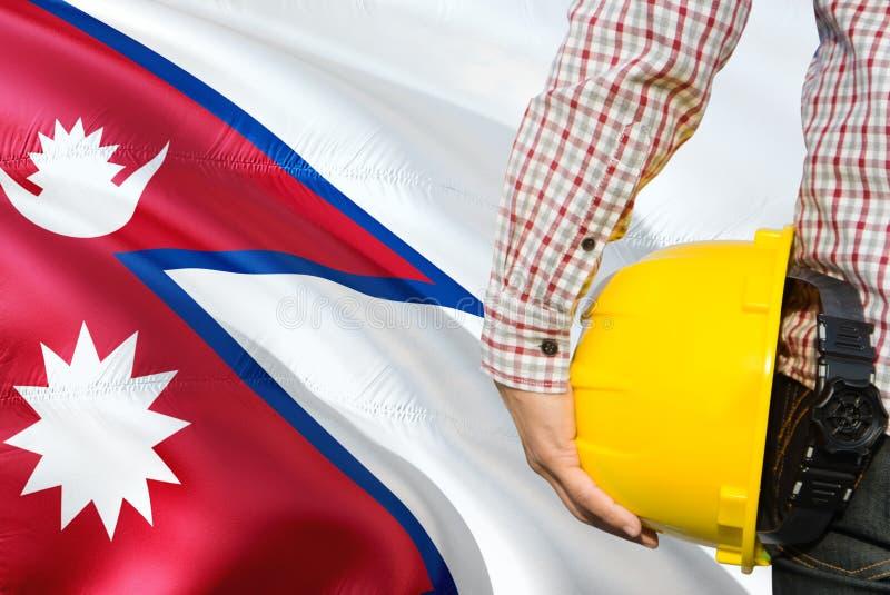 L'ingénieur népalais tient le casque de sécurité jaune avec onduler le fond de drapeau du Népal Concept de construction et de b?t photos libres de droits