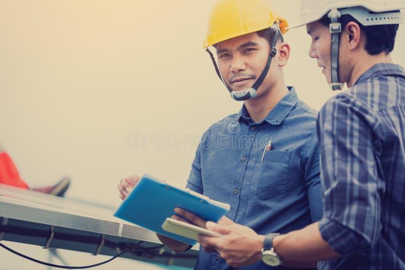 L'ingénieur ou l'électricien inspectent et vérifiant l'équipement solaire ; technologie futée pour l'opération de la centra photos libres de droits