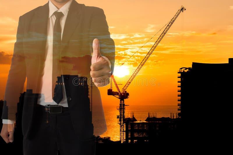 L'ingénieur ou l'homme d'affaires manie maladroitement vers le haut du geste avec la silhouette de la grue de chantier de constru image stock