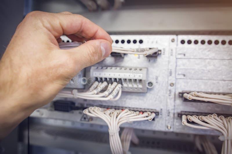 L'ingénieur relie des fils au connecteur du contrôleur industriel de contrôle en plan rapproché électrique de coffret images libres de droits