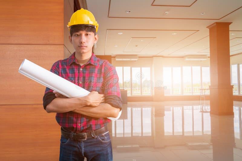 L'ingénieur signant décorent la pièce intérieure accomplie la main tenant les modèles roulés et les bras ont croisé casque jaune  photo stock
