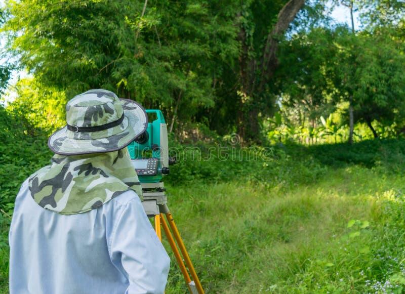 L'ingénieur travaille avec l'instrument de niveau-mesure pour l'enquête images libres de droits