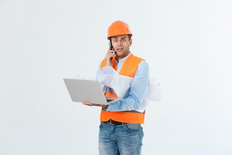 L'ingegnere, architetto, sul fronte occupato parla sullo smartphone mentre le tenute blueprints Uomo, caporeparto in casco che pa fotografia stock