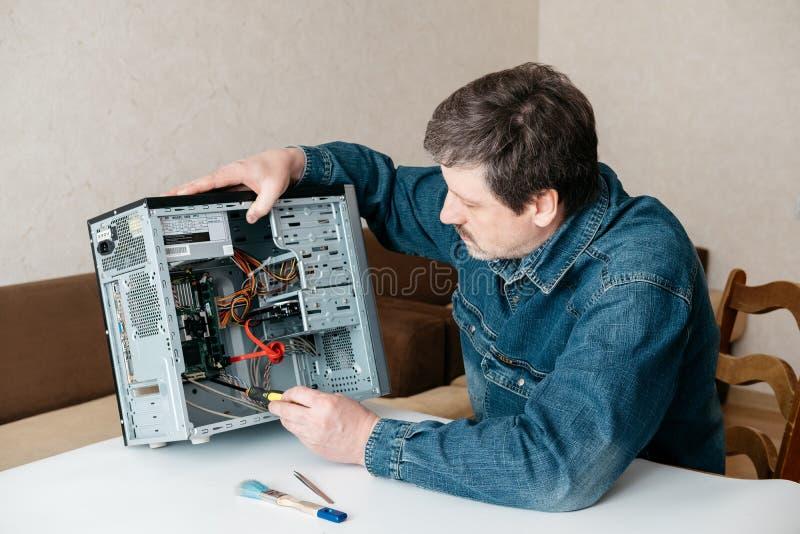 L'ingegnere del tecnico del computer con il cacciavite in sua mano sta riparando il personal computer immagine stock libera da diritti