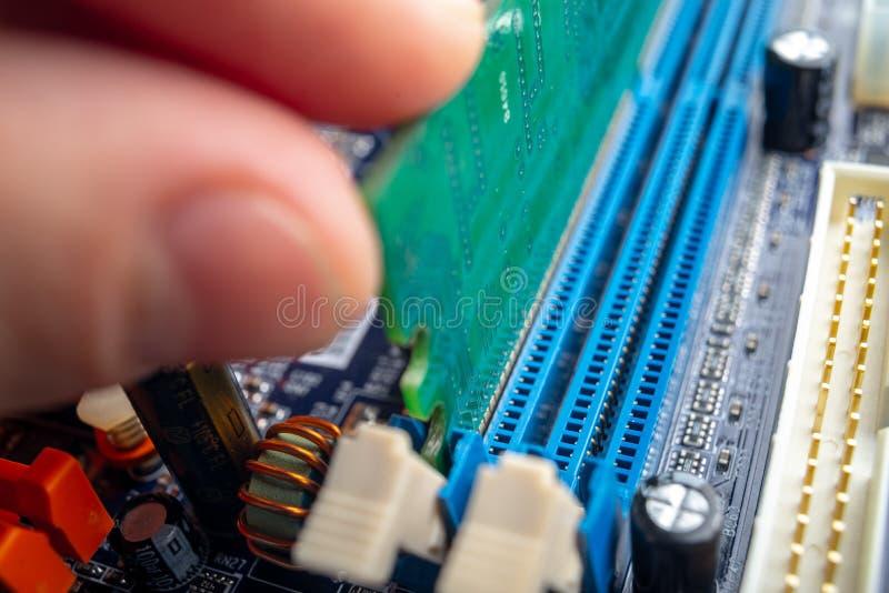 L'ingegnere del tecnico inserisce RAM nella scanalatura della scheda madre Il concetto del microchip di riparazione e di tecnolog immagine stock