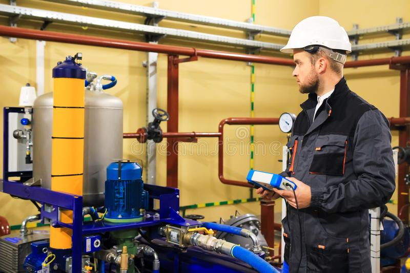 L'ingegnere del tecnico regola i sistemi di impianto idraulico fotografie stock libere da diritti