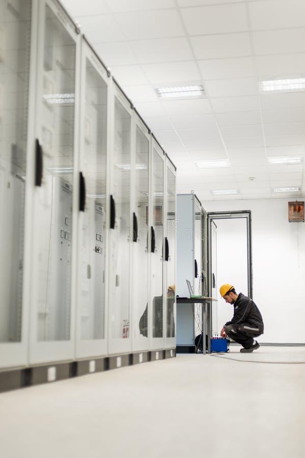 L'ingegnere di manutenzione ispeziona il sistema con i equipmen stabiliti della prova del relè immagini stock